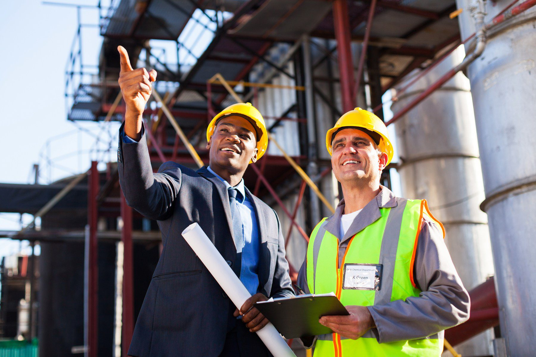 businessman with hard hat showing plant engineer something