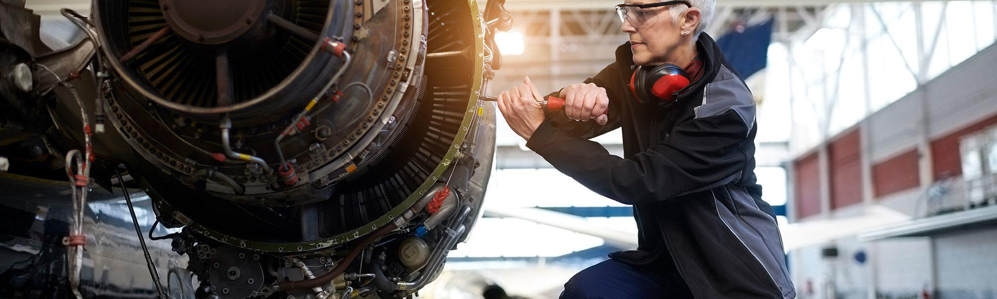 Aircraft being worked on by woman in industrial gear